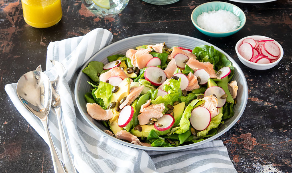 Pan-fried salmon with radish, avocado and pumpkin seed salad